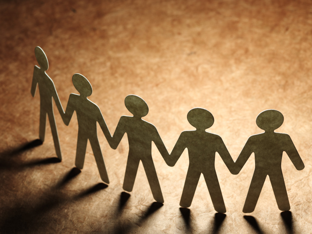 Group of paper people holding hands. Teamwork
